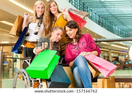 Four female friends with shopping bags having fun while shopping in a mall, stores in the background; one woman is sitting in a wheelchair - stock photo