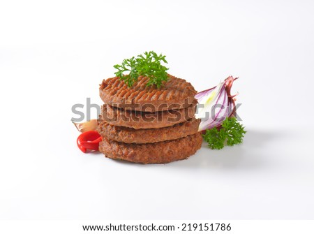 four flat beef burgers from the grill, decorated with herbs and onion