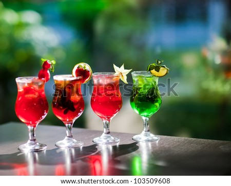 Four fresh drinks with strawberry and mint at the table outdoor