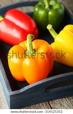 Four fresh pepper in blue tray on grey wooden background - stock photo
