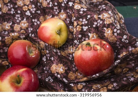 Four fresh tasty ripe clear fruits with vitamins of yellow red apple plum lying on brown fabric with floral pattern on wooden background, horizontal picture - stock photo