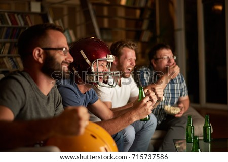 Four friends are watching american football game, cheering in front of television