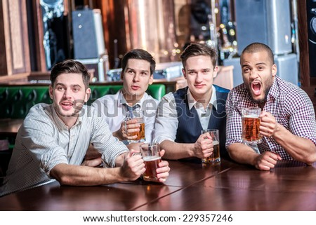Four friends businessmen drink beer and rejoice and shout together watching TV at the bar. Successful businessmen friends having fun together in the bar with a beer watching football on TV - stock photo