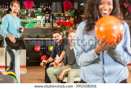 four friends  during a night out at a bowling alley, enjoying themselves in a competitive and active way, having fun, whilst one of them is ready to strike and throw the ball. - stock photo