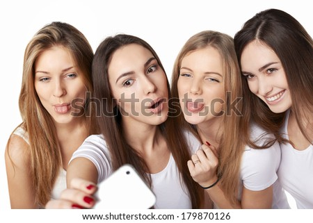 Four friends girls making self portrait with a smartphone, over white background - stock photo