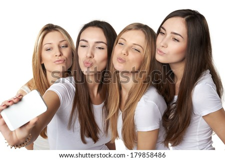 Four friends girls making self portrait with a smartphone, sending kisses, over white background - stock photo