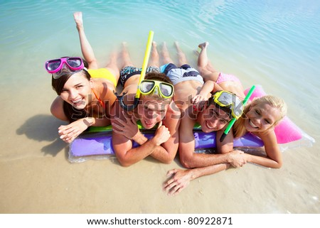 Four friends in scubas lying on sand by water - stock photo