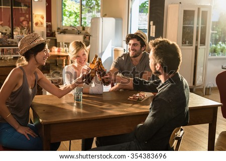 Four friends in their 30's having a drink after work. Two men and women are sitting at a wooden table joining their bottles of beer in a cozy house. They are smiling, wearing casual clothes and hats.