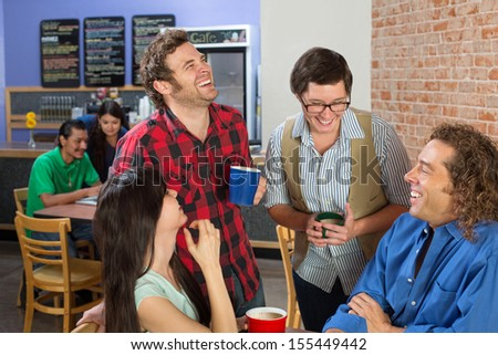 Four friends joking in a coffee house - stock photo