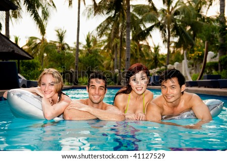 Four friends lying on an airbed in the swimming pool - stock photo