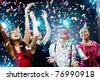 Four friends making having fun among confetti - stock photo