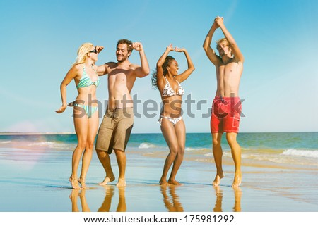 Four friends - men and women - on the ocean beach having lots of fun in their vacation jumping in the water - stock photo
