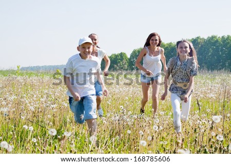 Four friends running at meadow in summer - stock photo