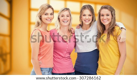 Four friends standing beside each other and smiling against room with large window showing city - stock photo