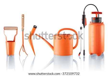 Four gardening tools and one pressure sprayer - stock photo