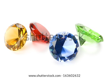 Four gemstones, yellow, red, blue and green isolated on white with soft shadows. Clipping path included.