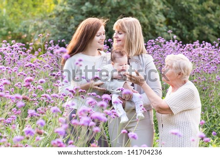 Four generations of beautiful women standing in a garden among red flowers - stock photo