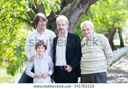 Four generations of men enjoying a nice summer day in the park - stock photo