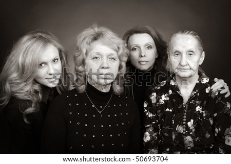 Four generations of women in a family on black - stock photo