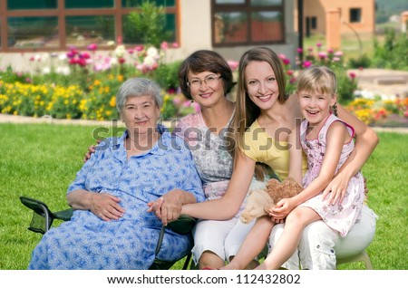 Four generations of women sitting together at countryside and smiling - stock photo