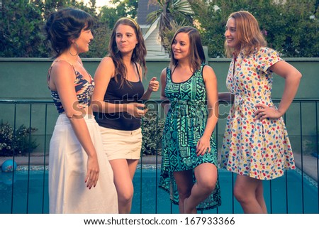 Four girl friends hanging out at the pool - stock photo