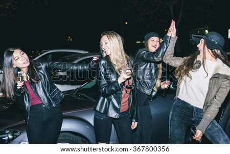 Four girls making party outdoor in the night. Image taken in the night with straight frontal flash light, for a realistic touch