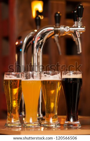 Four glasses of beer against beer tap - stock photo