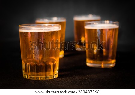 Four glasses of beer, one after another , isolated on black background - stock photo