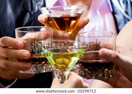 Four glasses touching in a toast - stock photo