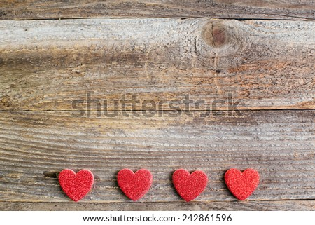 Four glitter hearts on reclaimed wood, valentines day background. - stock photo