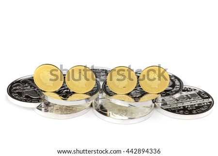 Four gold coins standing on silver coins isolated on white background - stock photo