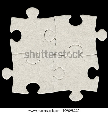 Four gray cardboard jigsaw puzzle pieces isolated on black - stock photo