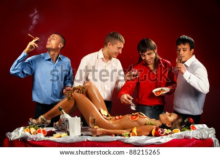Four guys having fun with woman decorated  by fruits - stock photo