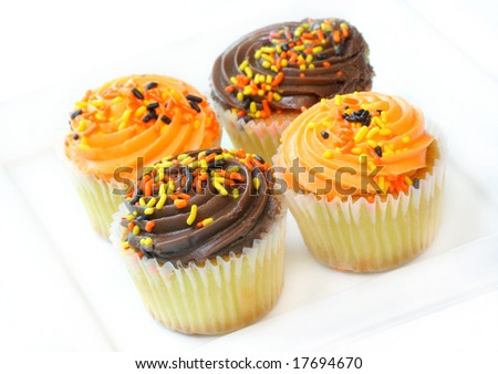 Four Halloween cupcakes on a white plate on a white background. - stock photo
