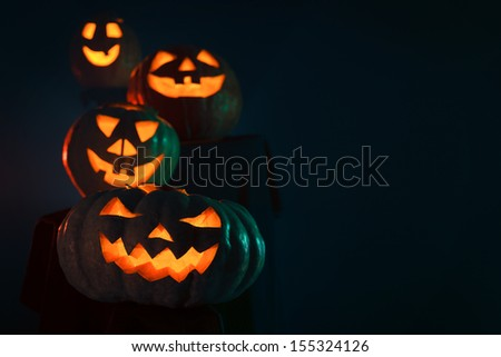 Four Halloween Pumpkin glowing in the dark with copy space - stock photo