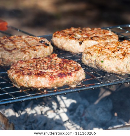 Four Hamburgers on Barbeque Grill - stock photo