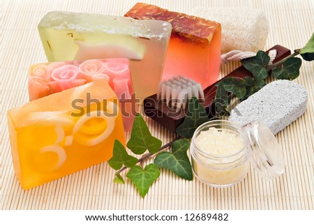 four handmade soaps with loofah brush and sea-salt on bamboo board
