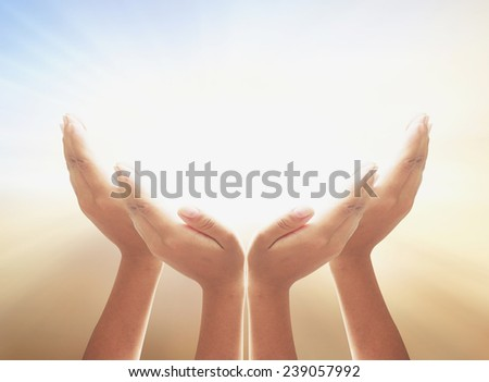 Four hands protecting something over the sunset. - stock photo
