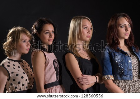 Four happy attractive female friends in party dresses standing arm in arm - stock photo