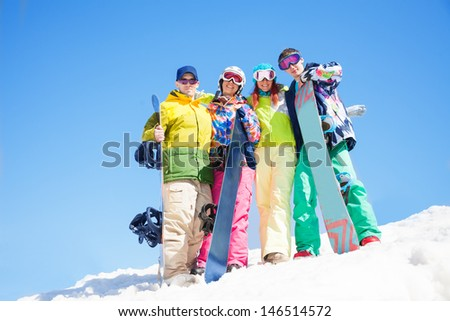 Four happy friends hug and hold snowboards standing in snow in winter - stock photo