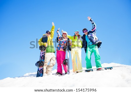 Four happy friends with snowboards standing in snow and waiting hands - stock photo