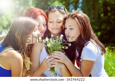 Four happy girl friends playing in green grass with wild flowers on summer field outdoors background - stock photo