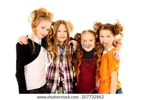 Four happy girls standing together and smiling at camera. Isolated over white. - stock photo