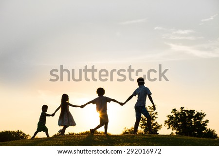 Four happy kids are playing on sunset. They jumping and holding by hands. - stock photo