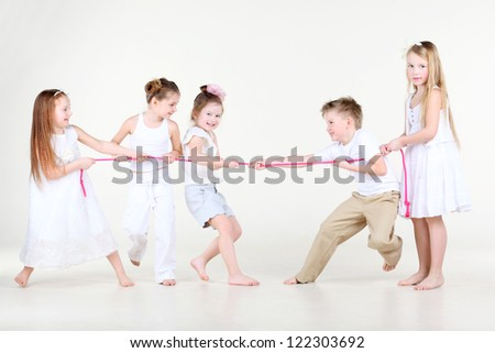 Four happy little girls and one boy in white clothes draw over pink rope. - stock photo