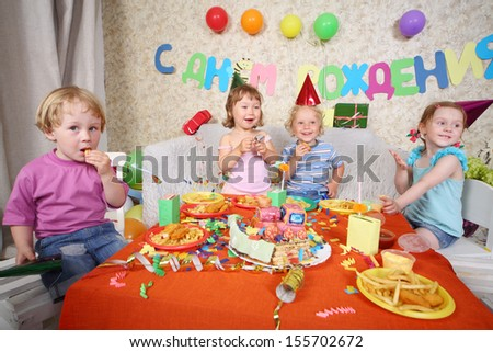 Four happy little kids eat fries with meat at red table with cake at birthday party. Inscription Happy Birthday on wall. - stock photo