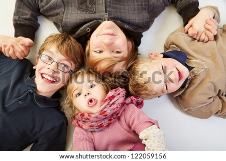 Four happy siblings in a circle looking up - stock photo
