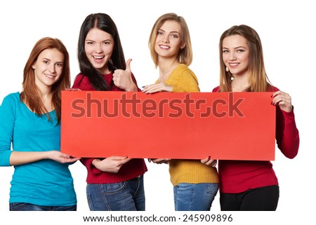 Four happy smiling girls friends holding red blank cardboard and gesturing thumbs up over white background - stock photo