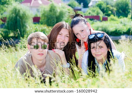 Four happy smiling & looking at camera teen friends girls and boy laying in green grass on summer outdoors background