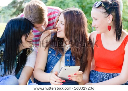 Four happy teen friends laughing on picture of themselves on tablet on summer outdoors background